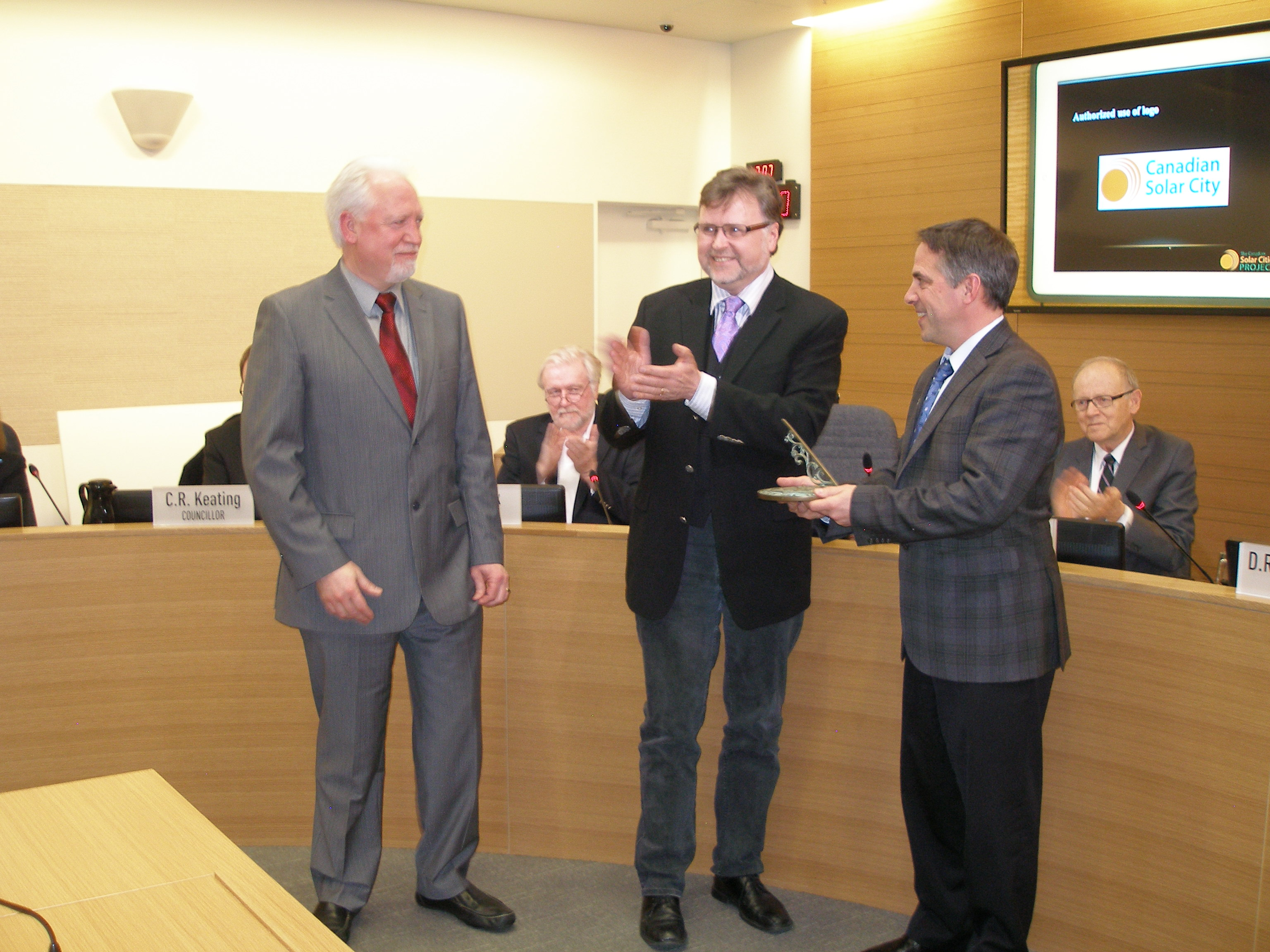 L-R, Executive Director Bob Haugen and Board Chairperson Walter Andreeff present Mayor Darrell Mussatto with a sundial in recognition of The City of North Vancouver's Canadian Solar City award.
